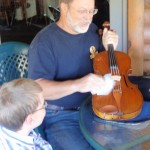 Odin's son Drew watching Scott doing repairs as resident luthier during the recent West Branch International Music Festival, NY.