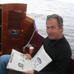 Russ reading the news of the day during the crossing to the St. Michaels Small Craft Festival