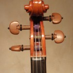 A hand-carved, Strad-style scroll and boxwood pegs.