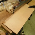 A shooting board is used to plane the top center joint prior to glueing.