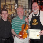 Harry Mayden, center with his finished violin. Gregg and Scott presenting tone and craftsmanship certificate.
