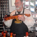 Instructor Scott W Hershey evaluating the craftsmanship of finished violins.